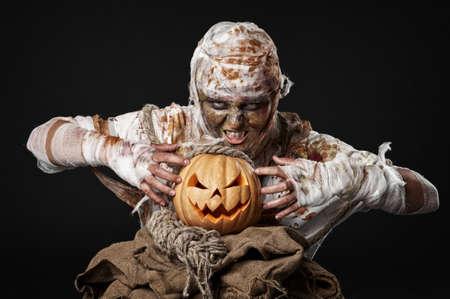 mummified: scary mummy holding the pumpkin in the studio