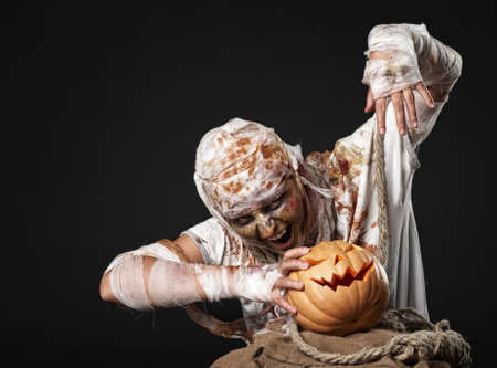 The mummy holding the pumpkin in the studio photo
