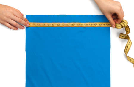 measures the size of a piece of blue cloth with a ruler Stock Photo - 17471704