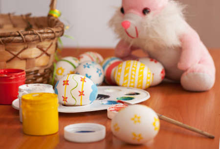 Easter eggs in the process of drawing with a rabbit in the background photo