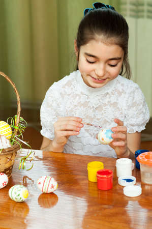 beautiful girl colored Easter eggs sitting at the table photo