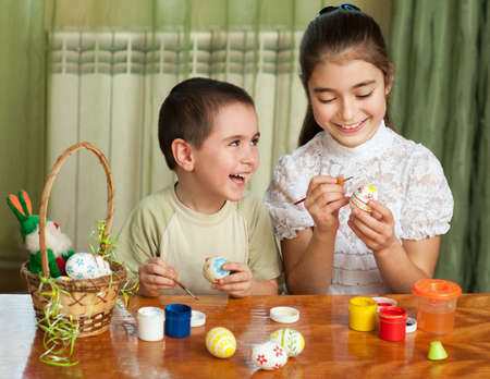 brother and sister painted Easter eggs at the table photo
