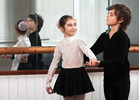 Boy and girl dancing in a ballet barre photo