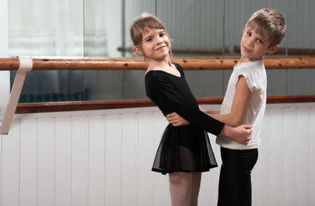 ballet child: Boy and girl dancing in a ballet barre