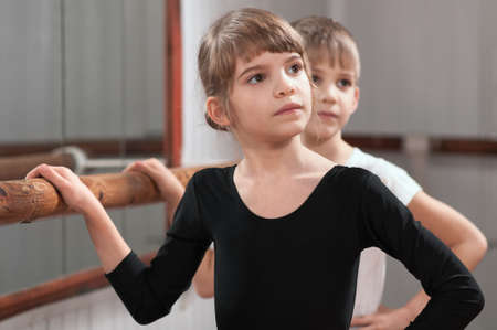 funny children learn to dance in the ballet barre photo