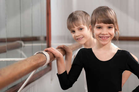 kids costume: funny children standing at ballet barre