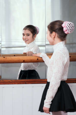 a beautiful girl standing at ballet barre and looks through the mirror photo
