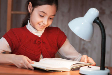 the girl at the desk reading a book by the light of the lamp