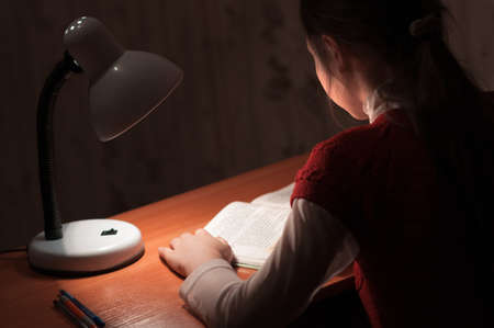 reading lamps: the girl at the desk reading a book by the light of the lamp