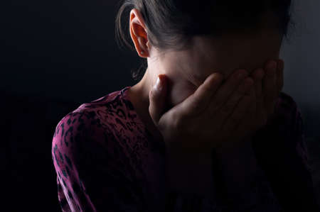 girl crying in the darkness covering her face
