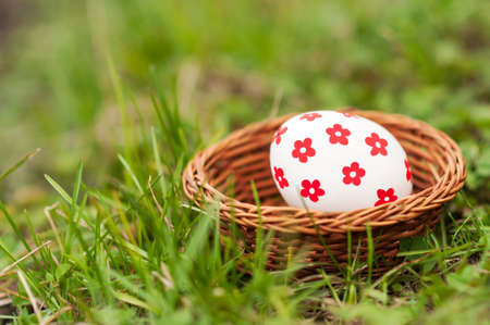 Easter Eggs in little basket on green grass photo