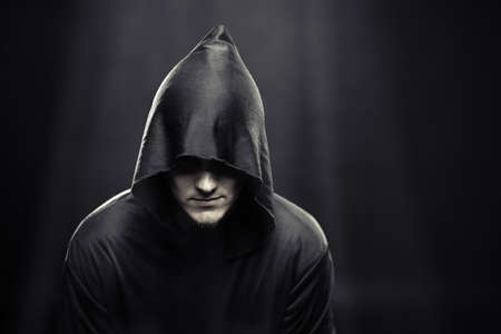 creed: a guy in a black robe standing in the dark under the rays of the moon