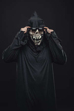 corrects: Skeleton in a black robe corrects glasses with both hands Stock Photo
