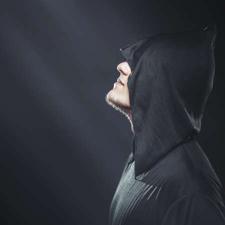 a guy in a black robe standing in the dark under the rays of the moon photo