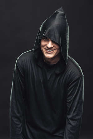 Cheerful guy in a black robe in the dark photo