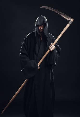 scythe: death with scythe standing in the dark Stock Photo