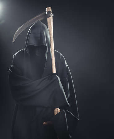 grim: death with scythe standing in the fog at night Stock Photo