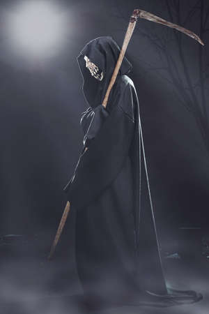 grim: death with scythe standing in the fog at night in the cemetery Stock Photo