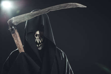 grim reaper: death with scythe standing in the dark Stock Photo