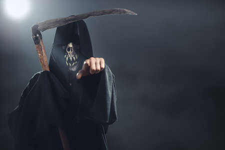 grim reaper: death with scythe standing in the fog at night and points to you Stock Photo