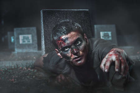 scary zombie crawls out of the grave at the cemetery photo