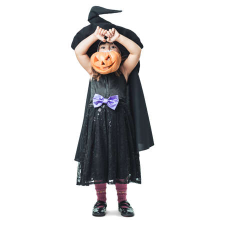 little witch shows the collected candy in pumpkin photo
