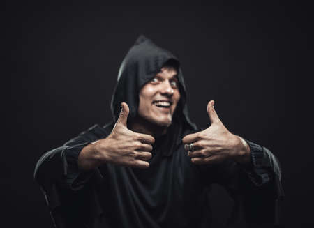 Smiling guy in a black robe showing thumbs up photo