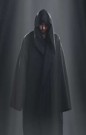 a guy in a black robe standing in the dark under the rays of the moon