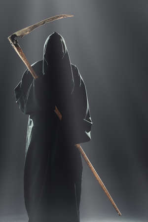 death with scythe standing in the fog at night photo