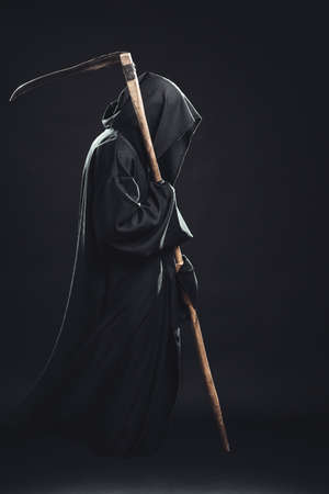 death with scythe standing in the dark 写真素材