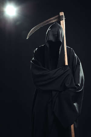 grim: death with scythe standing in the dark Stock Photo