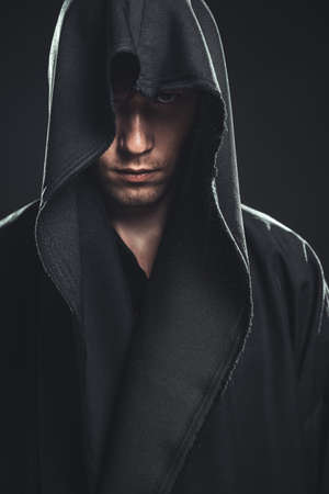 demon: serious guy in a black robe Stock Photo