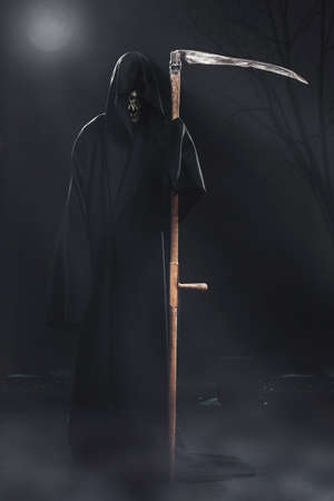 death with scythe standing in the fog at night in the cemetery photo