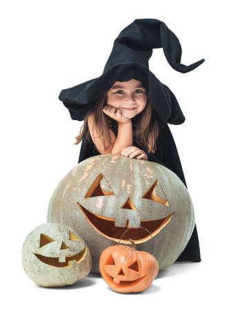 only child: fun little witch hiding behind pumpkins