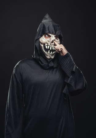 picks: scary skeleton in a robe picks his nose Stock Photo