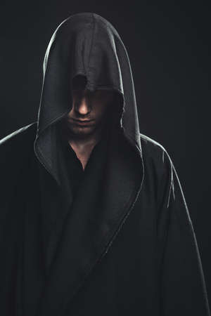 Portrait of a Man in a black robe on a dark background photo