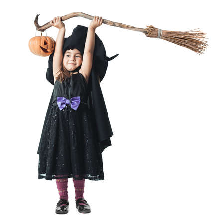 Little witch broom raised over his head with a pumpkin photo