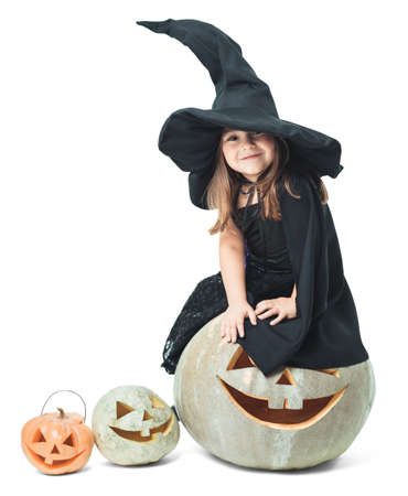 little witch sits on a halloween pumpkin Stock Photo