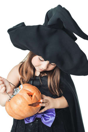 considers: little witch considers collected candy in pumpkin