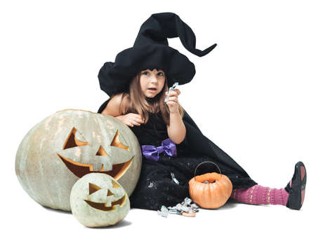 Little witch sits near the pumpkins and eating candy photo