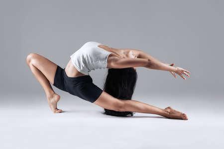 girl doing gymnastic poses in studio Stock Photo