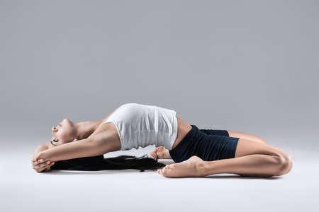 adult woman in supta virasana yoga position Stock Photo