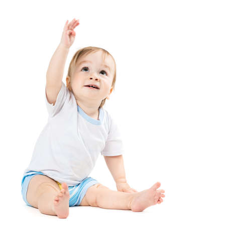 beautiful baby sitting and points his hand up
