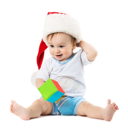 child in a hat santa scratches his head and holding a toy Stock Photo - 23572149