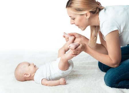 leg massage: Little baby with mum is making massage Editorial