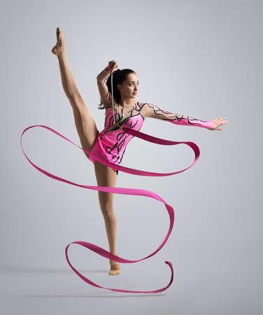 beautiful Caucasian girl gymnast with pink ribbon photo