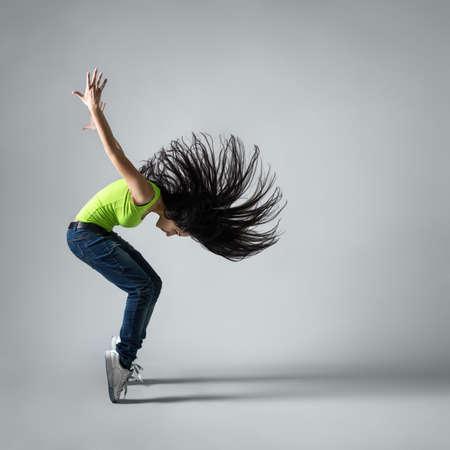 girl squatting: beautiful dancer girl squatting with flying black hair Stock Photo