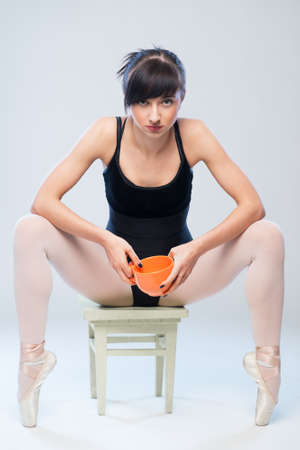 audacious: aggressive gymnast sitting on a chair with a cup in hands Stock Photo
