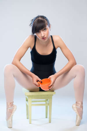 aggressive gymnast sitting on a chair with a cup in hands photo