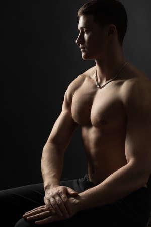 bodybuilder sitting and looking sideways at the dark photo